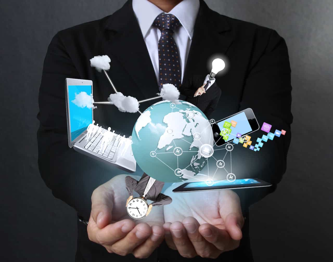 Business man with a globe, laptop, smart phone, tablet and watch projected and cradled in his hands