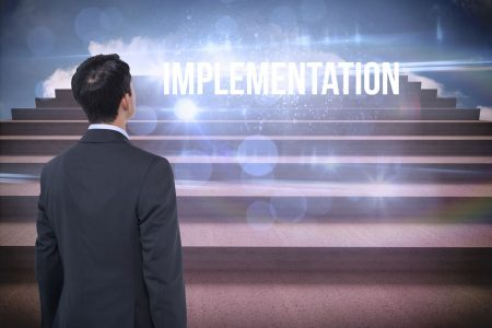 Business man standing with the word Implementation projected in front of him