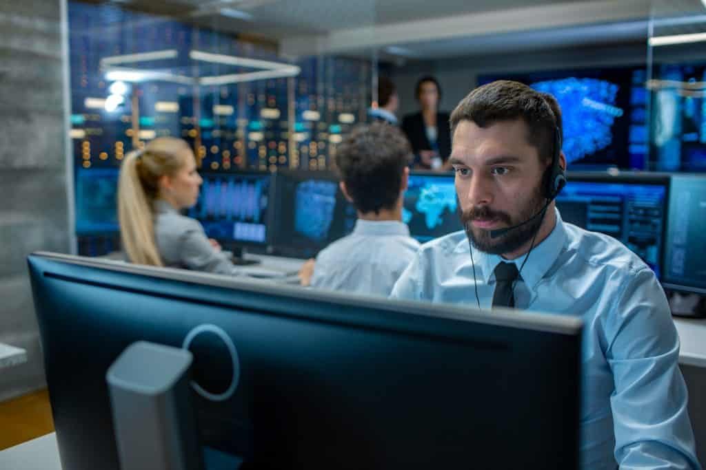 Man in computer control center monitoring cyber security